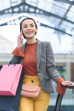 Photo pour Jolie femme parler de smartphone et portant des sacs de shopping au centre commercial - image libre de droit
