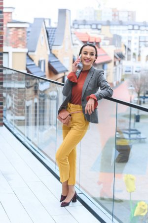 beautiful stylish woman standing on balcony and talking by smartphone
