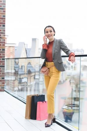 woman standing on mall balcony with shopping bags near legs and talking by smartphone
