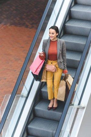 Photo pour Vue grand angle de jolie femme avec des sacs à provisions sur l'escalator dans centre commercial - image libre de droit