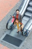 high angle view of attractive woman walking with shopping bags from escalator in mall