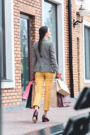rear view of woman walking with shopping bags