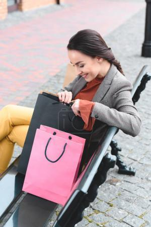 attractive woman sitting on bench and looking into shopping bag