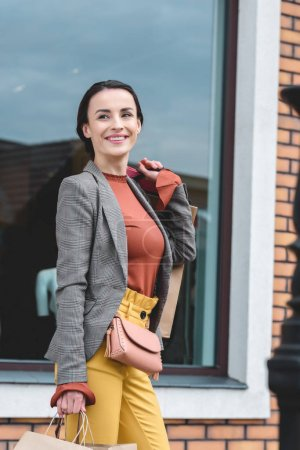 smiling attractive woman standing near showcase after shopping