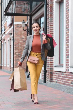 Photo pour Femme attrayante marchant avec des sacs à provisions sur l'épaule - image libre de droit