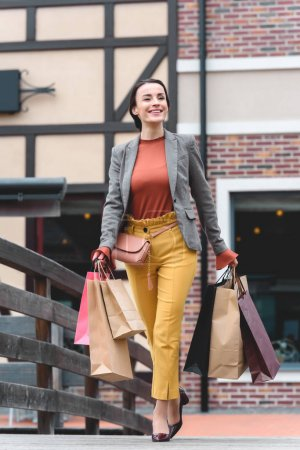 Photo for Attractive woman walking on bridge with shopping bags - Royalty Free Image
