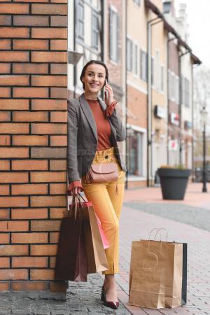 attractive woman leaning on wall after shopping and talking by smartphone