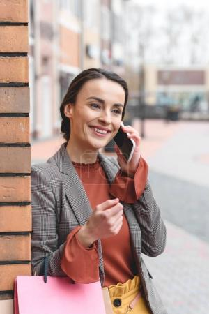 smiling attractive woman talking by smartphone and holding shopping bags