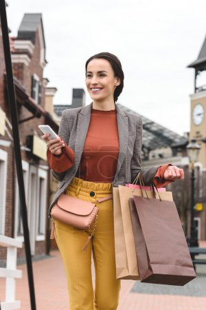 Photo for Smiling woman walking with shopping bags and smartphone - Royalty Free Image