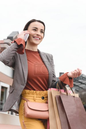 low angle view of attractive woman holding shopping bags and talking by smartphone