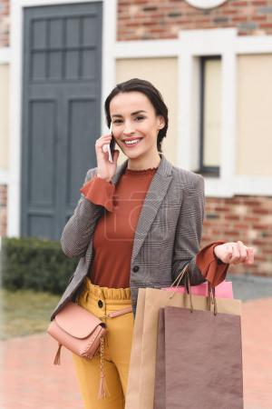 Photo pour Jolie femme tenant des sacs à provisions et parlant de smartphone dans rue - image libre de droit