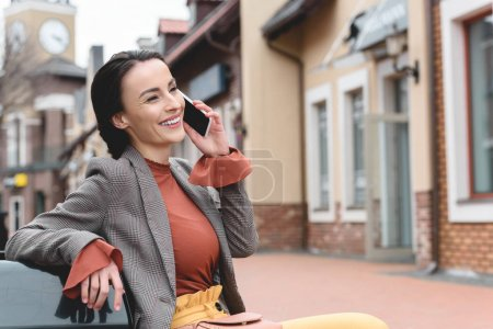 smiling beautiful stylish woman talking by smartphone on bench