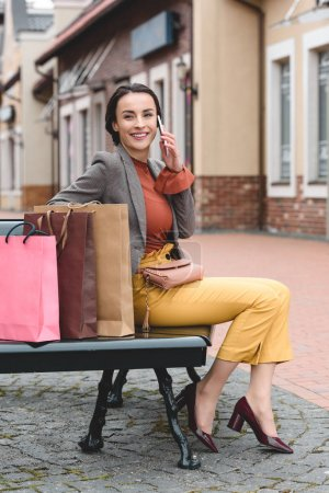 beautiful woman sitting on bench with shopping bags and talking by smartphone