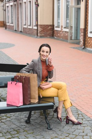attractive woman sitting on bench with shopping bags and talking by smartphone
