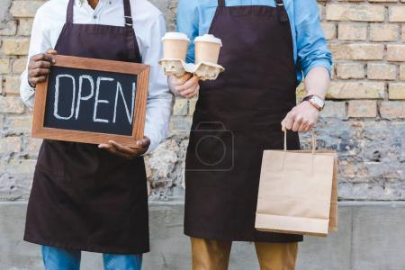 cropped shot of two multiethnic owners of coffee shop holding sign open, paper bags and disposable coffee cups while standing near brick wall