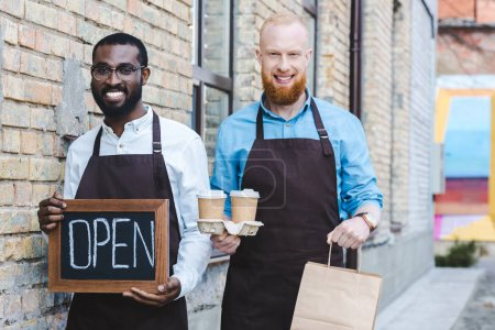 young handsome multiethnic owners of coffee shop in aprons with sign open, paper bags and disposable coffee cups smiling at camera