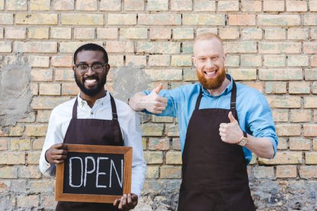 Handsome multiethnic owners of coffee shop in aprons holding sign open and showing thumbs up, smiling at camera