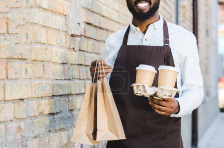 cropped shot of smiling young african american barista holding paper bags and disposable coffee cups