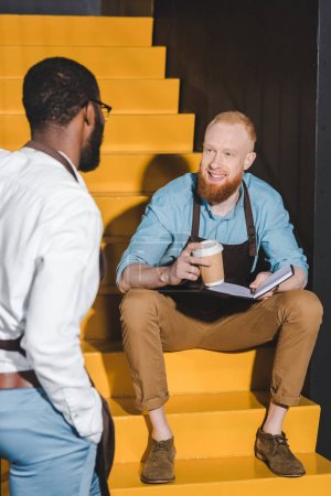 two multiethnic male baristas looking at each other and discussing work on stairs