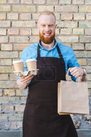 smiling young male barista in apron holding paper cups of coffee in cardboard and papers bags