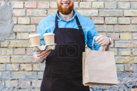 Photo for Cropped shot of smiling male barista in apron holding paper bags and disposable cups with coffee - Royalty Free Image
