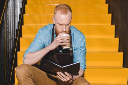 Photo pour Jeune mâle barista en tablier, boire du café de gobelet en papier et en regardant sur le manuel - image libre de droit