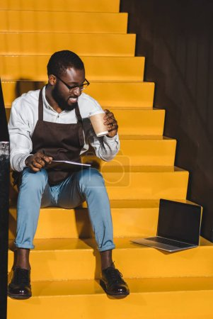 Photo for Smiling african american male barista with textbook drinking coffee and sitting on stairs with laptop - Royalty Free Image