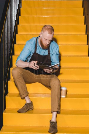 young male barista in apron holding textbook and sitting on stairs with disposable cup of coffee