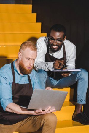 young male owners of coffee shop with textbook and laptop