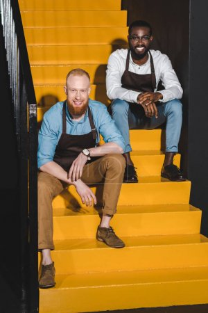 two smiling multiethnic owners of coffee shop in aprons sitting on stairs