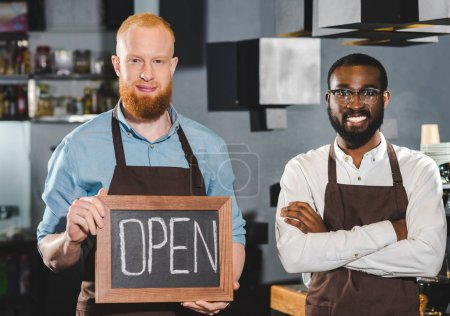 Photo for Smiling young multiethnic owners of coffee shop with blackboard with lettering open - Royalty Free Image