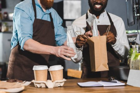 cropped image of owners of coffee shop putting order in paper bag