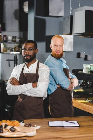two young multicultural male baristas in aprons standing with crossed arms in coffee shop