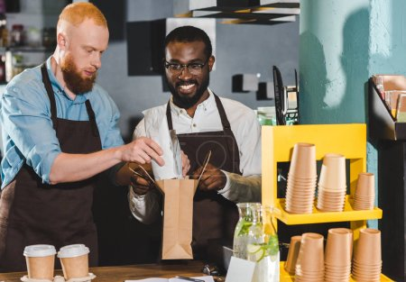 smiling  young multiethnic owners of coffee shop putting order in paper bag