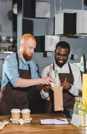 two young multiethnic owners of coffee shop putting order in paper bag
