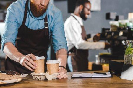 Photo pour Photo recadrée de mâle barista en tablier mettre les gobelets en papier de café en carton et souriant collègue à l'aide de la machine à café derrière - image libre de droit