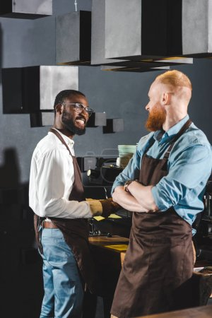 young smiling multiethnic owners of coffee shop in aprons talking in coffee shop