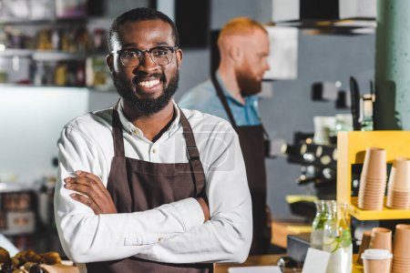portrait of young smiling african american male barista in apron with colleague standing behind