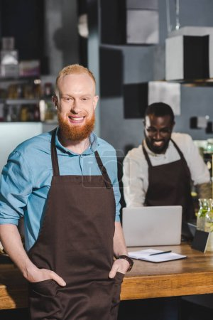 smiling young male barista in apron with colleague in coffee shop