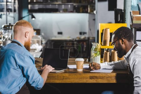 young male multiethnic owners of coffee shop working at table with textbook and laptop