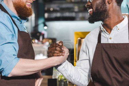 cropped image of two smiling owners of coffee shop shaking hands
