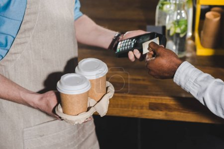 cropped shot of client paying by credit card and barista with terminal and coffee cups in hands