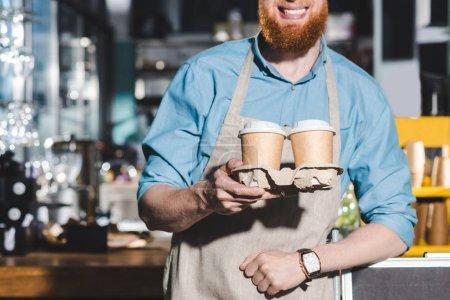 Cropped image du sourire masculin barista tenant deux tasses jetables de café