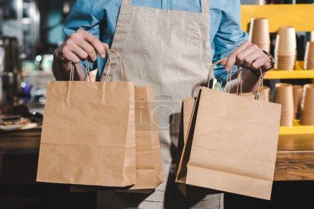 Photo pour Plan recadré de barista mâle dans un tablier tenant des sacs en papier dans un café - image libre de droit
