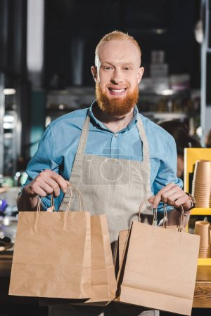 young male barista in apron holding paper bags in coffee shop