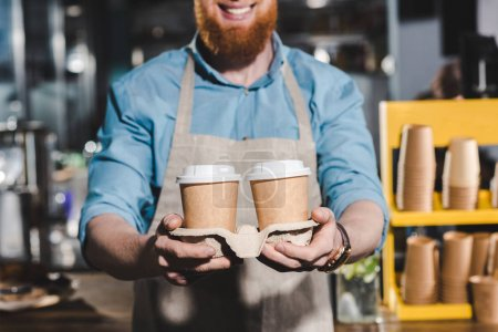 cropped image of smiling male barista holding two disposable cups of coffee