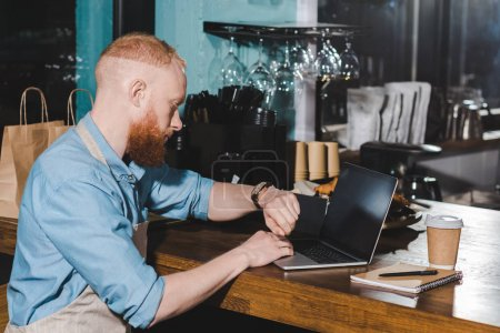 young male barista looking at wristwatch and sitting at table with laptop in coffee shop