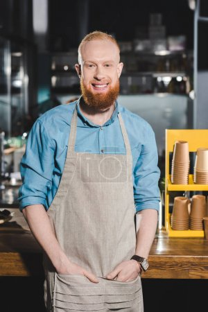 smiling young male barista in apron standing in coffee shop