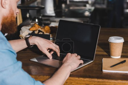 cropped image of young male barista sitting at table with laptop
