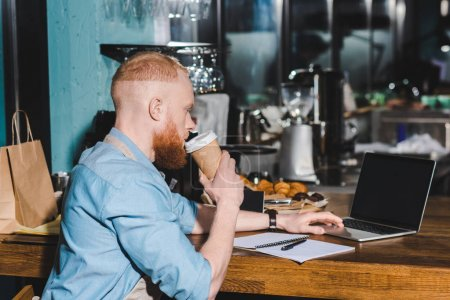 side view of young male barista drinking coffee from paper cup and using laptop